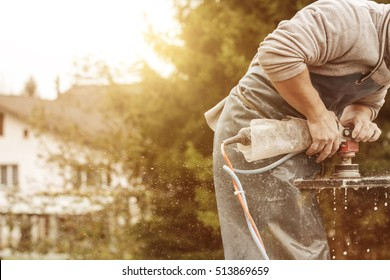 handyman working with grinding machine on a stone plate in the sunlight