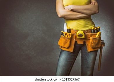 Handywoman with folded arms and tool belt on concrete background.