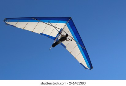 Hang Glider flying in the sky on a sunny bright blue day