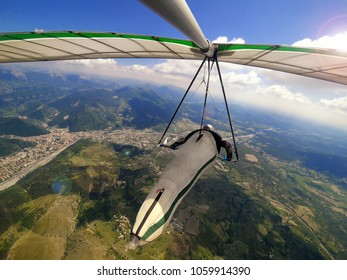 Hang glider pilot flies high over alpine terrain during hanggliding competition in Provance, France. Action camera shot of extreme sport