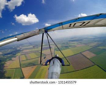 Hang glider pilot fly high over endless green fields. Aerial photo of extreme sport