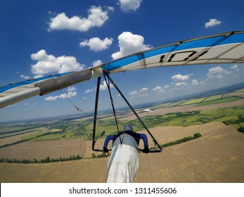 Hang glider pilot fly high above terrain. Action camera shot of extreme sport