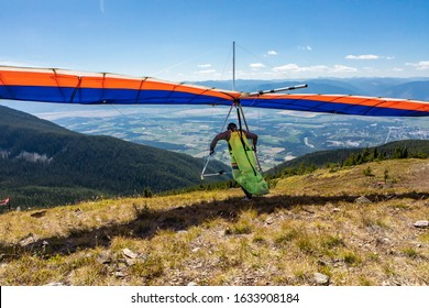 Hang glider pilot running and taking off. Scenic view over Kootenay valley mountains. View from behind to flying Hang glider