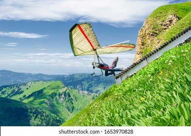 Hang glider pilots runs from steep slope high in the mountains. Diedamskopf, Austria. Extreme airborne sport.