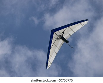 Hang glider soaring against a beautiful cloudscape