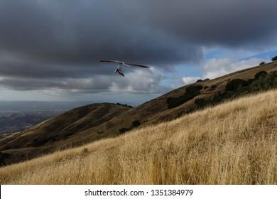 Hang glider takes off above grassy hills of mt Diablo below dark heavy storm clouds