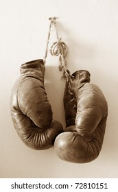 hang up the gloves, old worn leather boxing gloves in sepia tones, hanged up on grunge style wall.