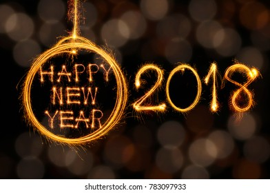 Hang Happy new year text in ball and 2018 written with sparkle fireworks on gold bokeh background