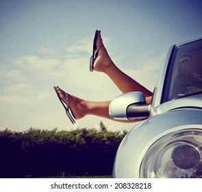 Hang loose - Road trip concept. Woman Hangs Her legs out of window in car.