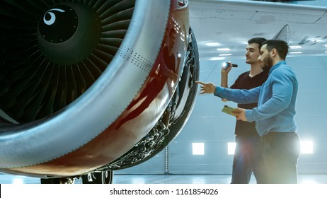 In a Hangar Aircraft Maintenance Engineer Shows Technical Data on Tablet Computer to Airplane Technician, They Diagnose Jet Engine Through Open Hatch. They Stand Near Clean Brand New Plane.