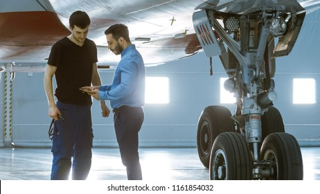 In a Hangar Aircraft Maintenance Engineer Shows  Technical Data on Tablet Computer to Airplane Technician. They Stand Near Clean Brand New Plane.