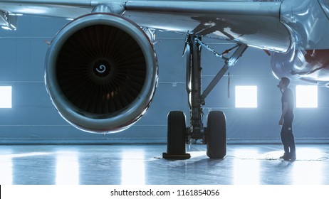 In a Hangar Aircraft Maintenance Engineer/ Technician/ Mechanic Visually Inspects Airplane's Jet Engine.