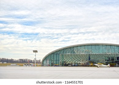 hangar with airplane and blue sky. A small plane stands near the hangar and is preparing to take off. Hangar from glass.