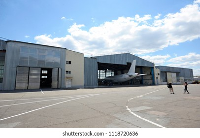"Hangars situated on a plant territory, airbus A320 standing in one of them, people walking around. Press-tour to the State Aircraft Repair Plant ""410"". June 7, 2018. Kiev, Ukraine"