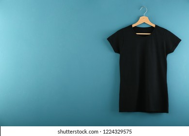 Hanger with blank black t-shirt on color background