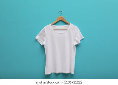 Hanger with blank t-shirt on color background. Mockup for design