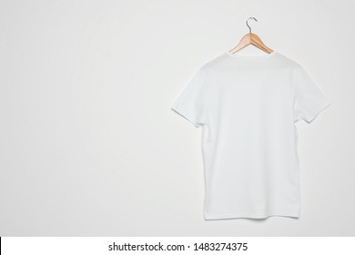 Hanger with blank t-shirt on white background. Mock up for design