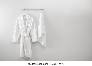 Hanger with clean bathrobe and towel on light wall. Space for text