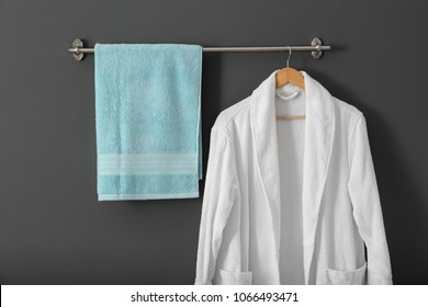 Hanger with clean towel and bathrobe on grey wall
