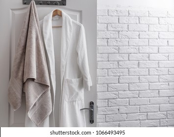 Hanger with clean towel and bathrobe on door