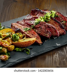Hanger medium-rare stake with vegetables garnish on a black stone board. Delicious dinner.