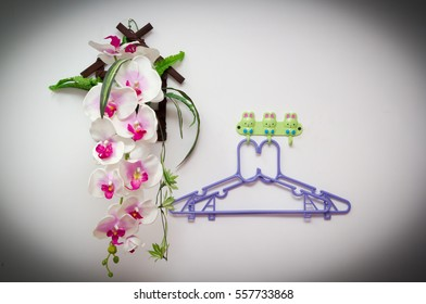 Hanger on white wall near fake orchid.