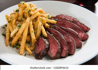 Hanger Steak with French Fries served with wine on a white plate