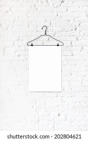 Hanger with white paper on a white brick wall