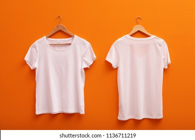 Hangers with blank t-shirts on color background. Mockup for design