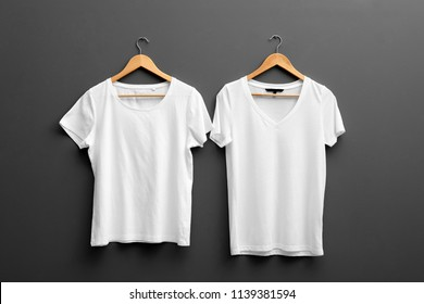 Hangers with blank t-shirts on grey background. Mockup for design