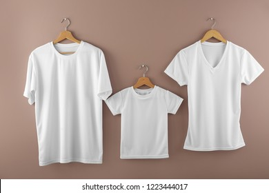 Hangers with blank white t-shirts on color background