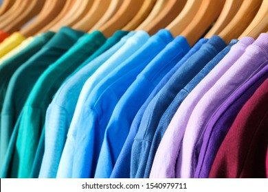 Hangers with bright clothes as background, closeup