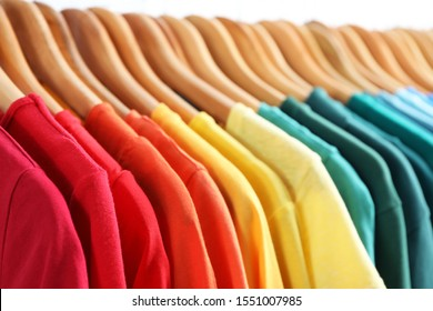 Hangers with bright clothes on light background, closeup