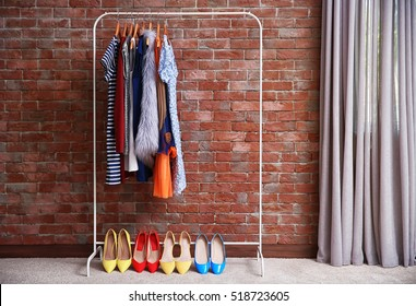Hangers with different female clothes on brick wall background