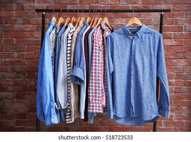 Hangers with different male clothes on brick wall background