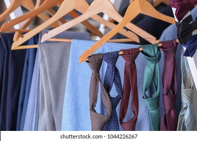 Hangers with suits and ties in tailor's workshop