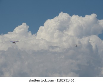 Hang-gliders fly take off towards a developing thunderstorm cumulonimbus cloud in the San Luis Valley of southern Colorado.