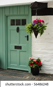Hanging basket on Oak beam with copy space front door and pot plant.