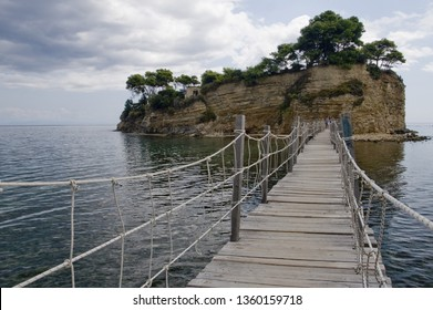 Hanging bridge to the Cameo island, the most picturesque place in Laganas Bay, with pine trees growing in the rocks and  white cloth blowing in the wind, Agios Sostis, Zakynthos, Greece