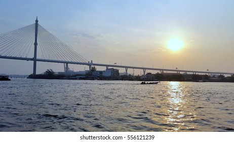 Hanging bridge cross Chao pha ya river in Thailand connect industrial area, and morning sky, view from ferry.