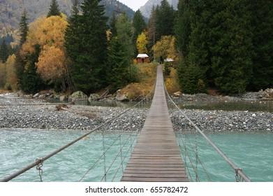 Hanging bridge over river against autumn forest.