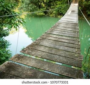 Hanging bridge over river in jungle of Rio Blanco National Park in Toledo Belize