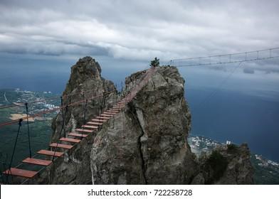 Hanging bridge in steep rocks at dramatic overcast weather. Ai-Petri, Crimea.