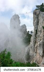 Hanging bridge in steep rocks with going man. Ai-Petri, Crimea.