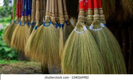 Hanging broomsticks made of grass and bamboo being sold on a roadside shop. Close up.