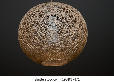 hanging from the ceiling is a decorative lampshade made of twine, with an energy-saving lamp turned on. Chandelier made of braided rope