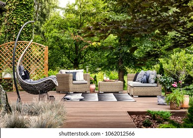Hanging chair and geometric carpet on wooden patio with rattan garden furniture