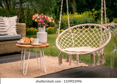 Hanging chair next to table with flowers on terrace in the garden during spring. Real photo