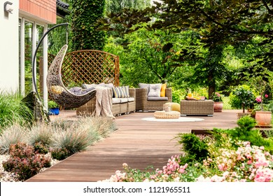 Hanging chair and pouf on wooden veranda in the middle of garden with flowers. Real photo