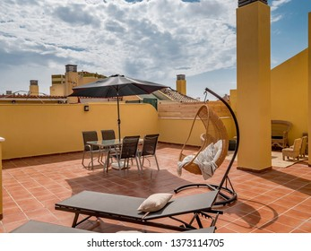Hanging chair and sun beds in a sunny terrace of a relaxing summer holiday destination with sea view. Idyllic holidays concept.